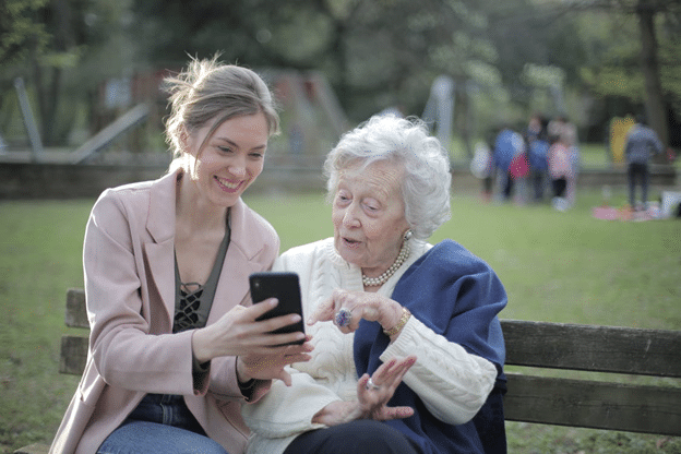 Young and aged woman looking at a phone